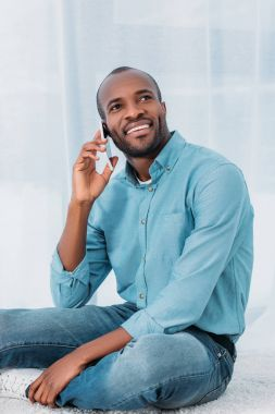 Smiling african american man sitting on floor and talking by smartphone at home stock vector