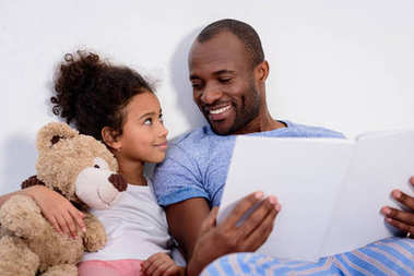 african american father holding book and looking at daughter at home