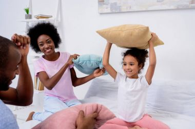 african american parents and daughter playing with pillows at home