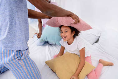 cropped image of african american parents and daughter playing with pillows at home