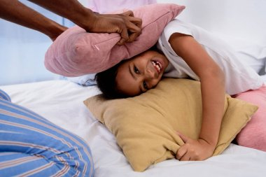 cropped image of african american father and daughter playing with pillows