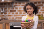 Fotografie adorable african american kid holding straw basket with painted easter eggs