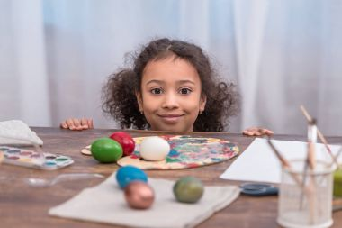 adorable african american kid looking at camera near table with easter eggs