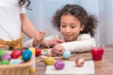 cropped image of african american mother and daughter painting easter eggs