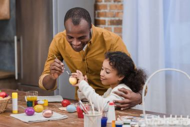 happy african american father and daughter painting easter eggs