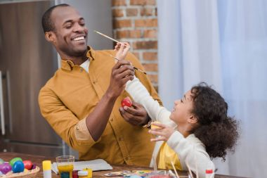 african american father and daughter having fun while painting easter eggs