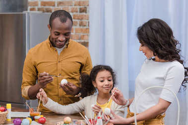 happy african american family painting easter eggs