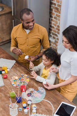 high angle view of african american family painting easter eggs
