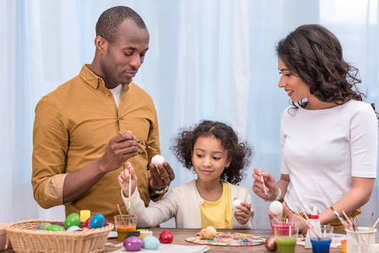 african american parents and daughter painting chicken easter eggs