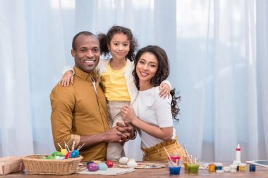 happy african american family looking at camera, easter concept