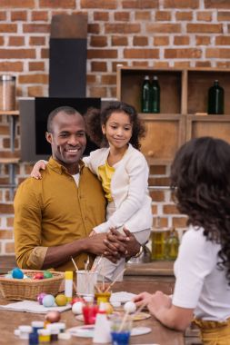 african american father carrying daughter, mother standing at table with easter eggs