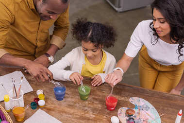 high angle view of african american parents and daughter painting easter eggs in glasses with paints