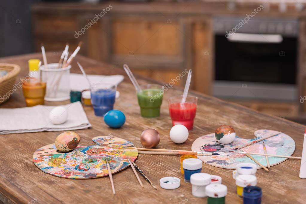 painted chicken eggs with paints and brushes on wooden table, easter concept