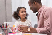 Fotografie happy african american father and daughter making greeting card on mothers day and looking at each other