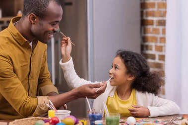 african american father and daughter having fun and painting faces, easter concept