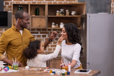 side view of african american daughter and father painting mother face with paints, easter concept