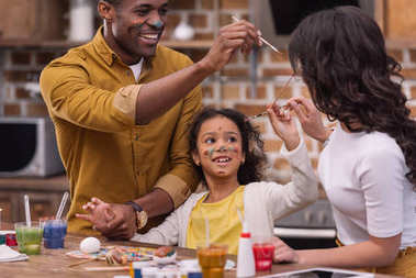 african american parents and daughter having fun while painting easter eggs