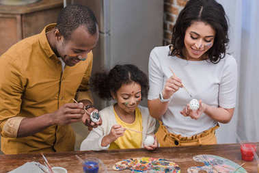 happy african american parents and daughter painting easter eggs