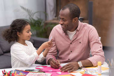 smiling african american father and daughter making greeting card on mothers day