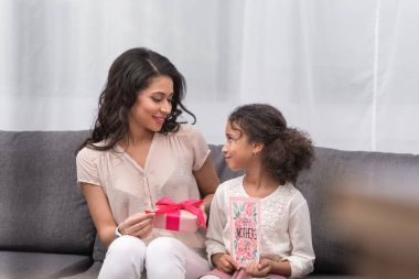 african american daughter presenting gifts to mother on mothers day at home