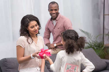 african american daughter presenting gifts to mother on mothers day