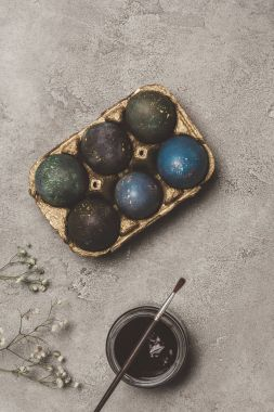 top view of painted easter eggs in golden tray with paint and brush on concrete