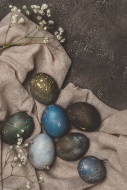 top view of shabby painted easter eggs and flowers on tablecloth