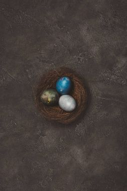 top view of nest with three painted easter egg on concrete table