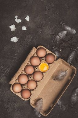 top view of chicken eggs and one broken egg with yolk in cardboard tray with feathers and branches on table