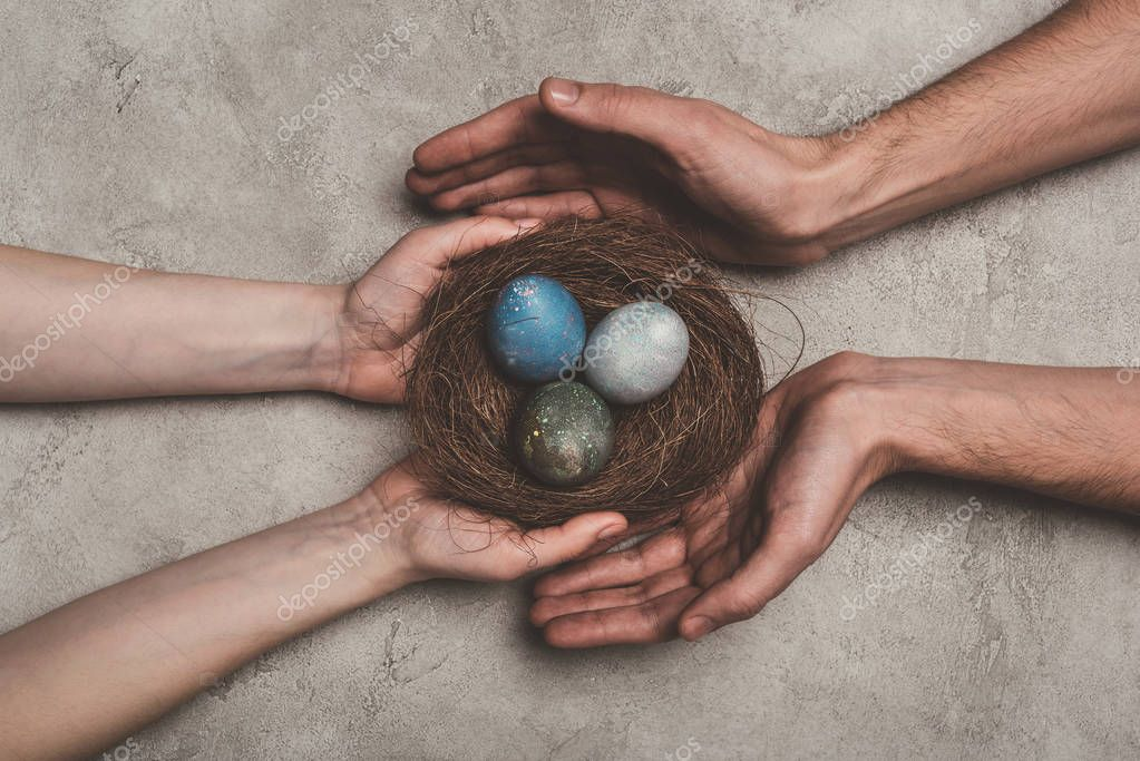 cropped view of couple holding nest with painted easter eggs on concrete surface