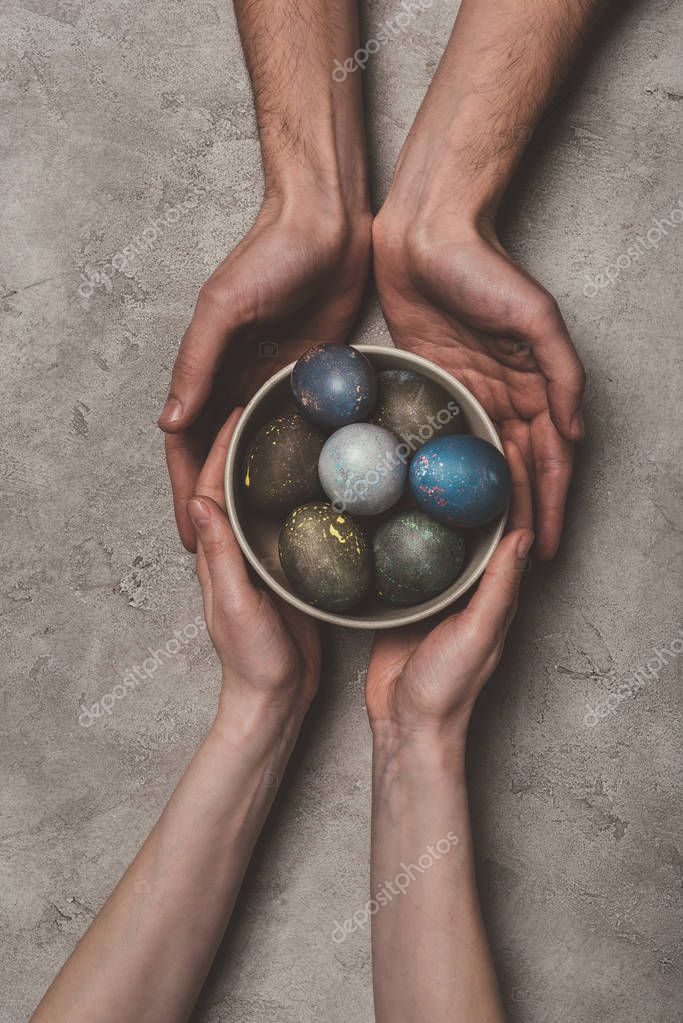 cropped view of couple holding bowl with painted easter eggs