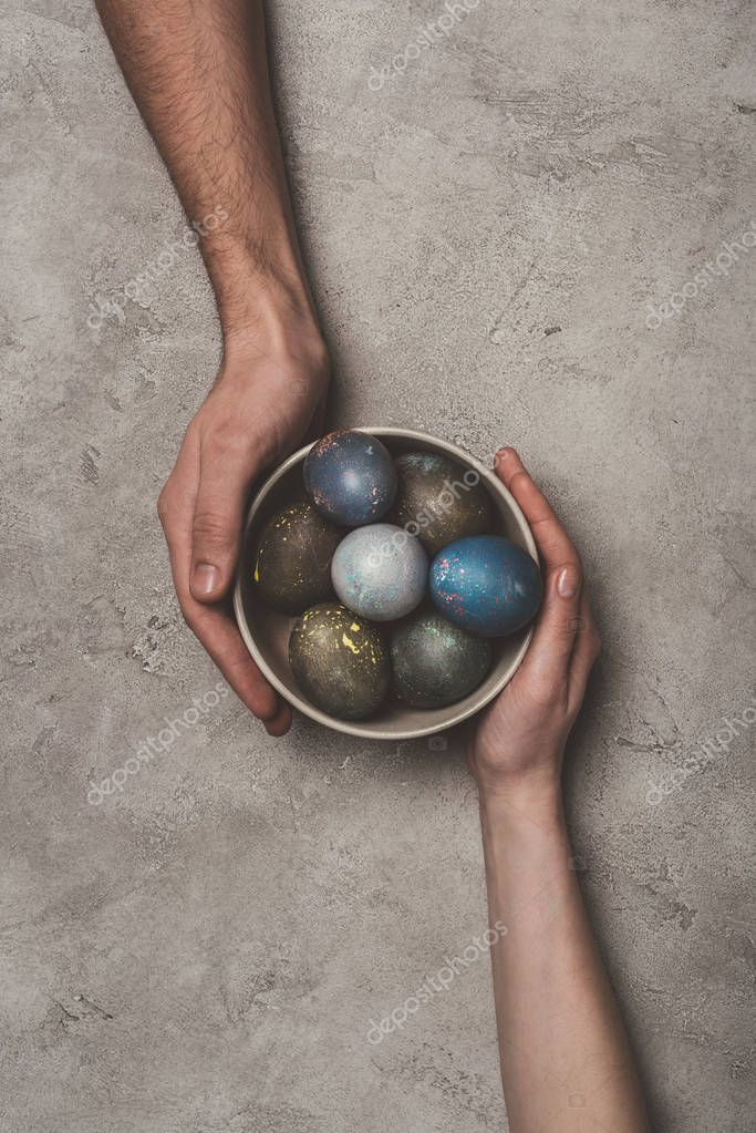 cropped view of couple holding bowl with easter eggs on concrete surface
