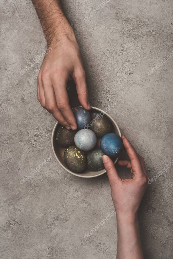 cropped view of couple with bowl of easter eggs on concrete surface