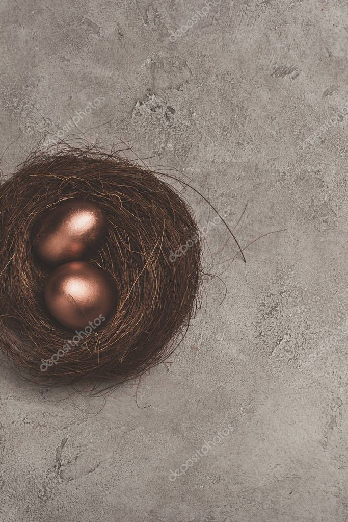 top view of golden easter eggs in nest on concrete surface