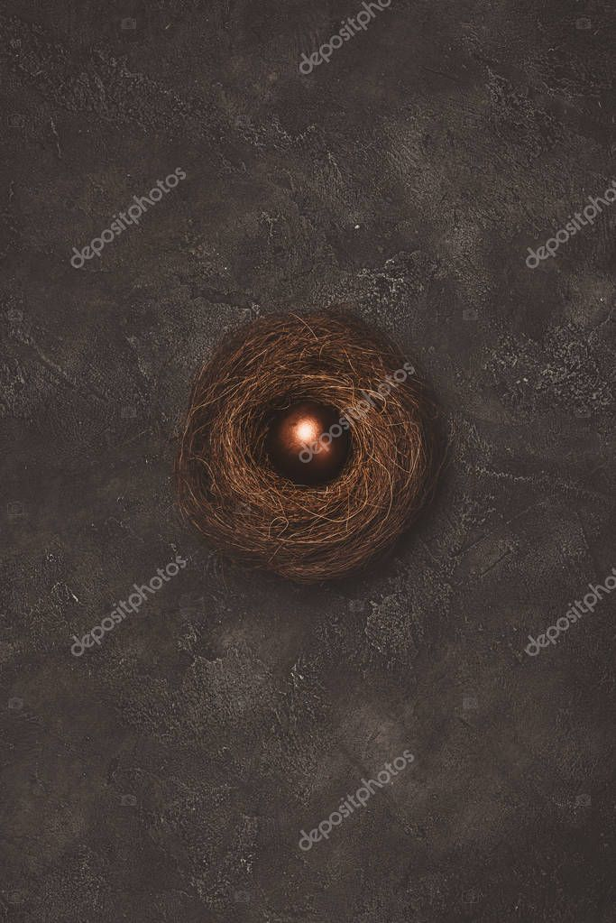 top view of golden easter egg in nest on concrete surface