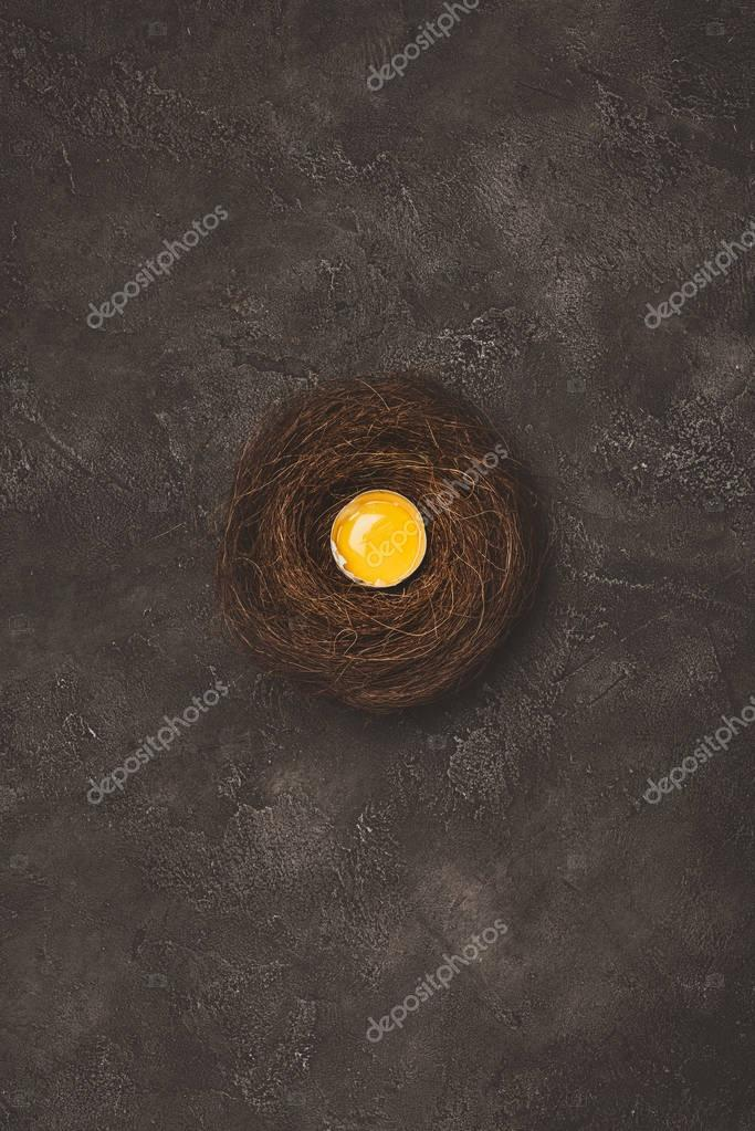 top view of broken egg with yolk in nest on concrete surface