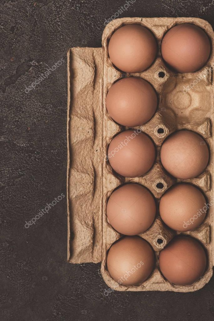 top view of chicken eggs in cardboard tray on grey