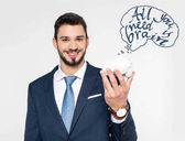 young businessman holding brain model with inscription all you need is brain and smiling at camera isolated on grey