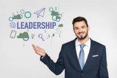 Fotografie schöner junger Geschäftsmann zeigt Führungs-Ikonen und lächelt isoliert in die Kamera auf grau