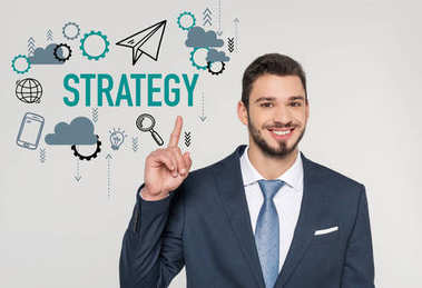 smiling young businessman pointing up with finger and looking at camera, strategy concept