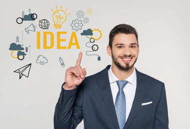 smiling young businessman pointing up with finger and looking at camera, idea concept