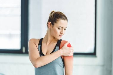 portrait of young sportswoman suffering from pain in arm at gym