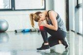 vista laterale di giovane donna in abbigliamento sportivo avendo dolore nel ginocchio durante lallenamento in palestra