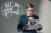 portrét pohledný stylový podnikatel v brýlích na čtení novin a vše co potřebujete je mozek nápis na grey