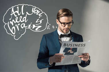 portrait of handsome stylish businessman in spectacles reading newspaper and all you need is brain inscription on grey