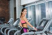 Fotografie Sportliche Frau steht auf Laufband und blickt in Kamera