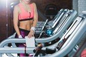 Fotografie abgeschnittenes Bild einer sportlichen Frau, die auf Laufband steht und Handtuch berührt