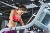 Fotografie müde Sportlerin stehend auf Laufband im Fitness-Studio