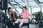 Fotografie overweight woman working out on training apparatus while trainer watching her