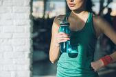 Fotografie oříznutý obraz sportovní ženy držící láhev vody